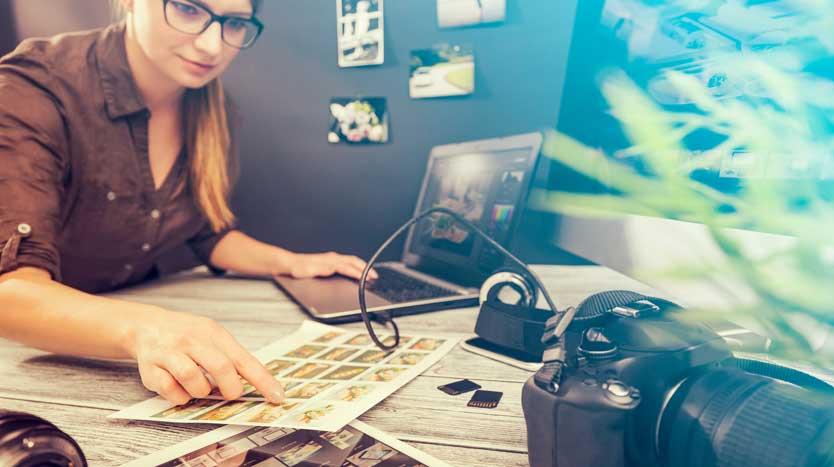 Fotografin arbeitet am Laptop und inspiziert Bildabzüge