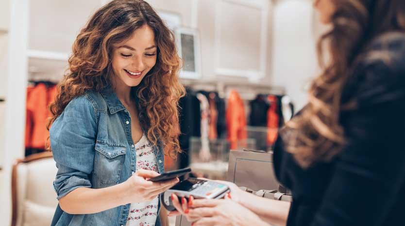 Junge Frau bezahlt im Modekaufhaus mit dem Smartphone