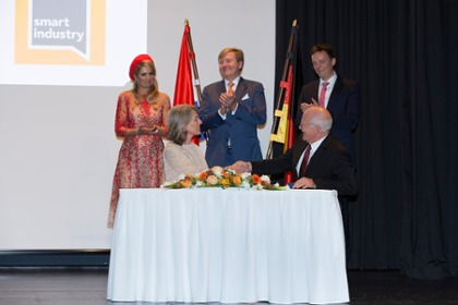 Thomas Hahn (Plattform Industrie 4.0) and Ineke Dezentje Hamming-Bluemink, (Smart Industry) at the signing of the agreement. In the background: the Dutch royal couple, Máxima and Willem-Alexander.