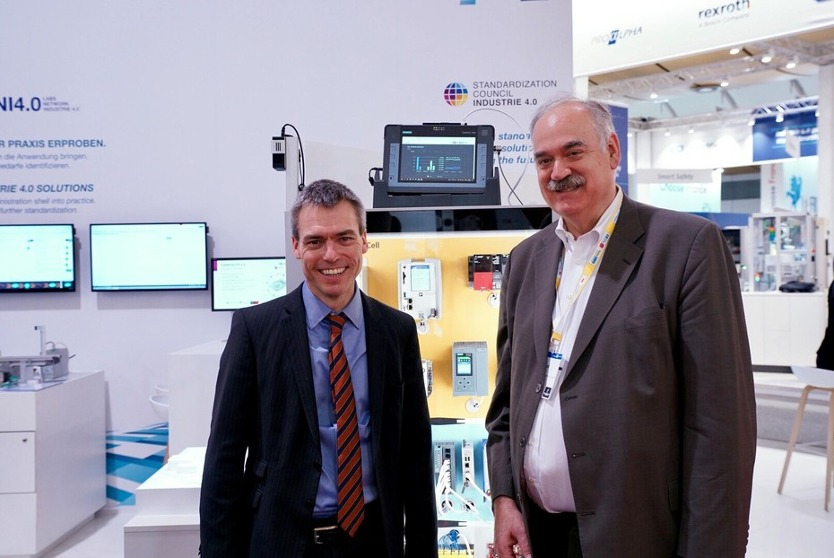 Henning Banthien (Plattform Industrie 4.0 Secretary General, l.) and Dr. Richard Mark Soley (Executive Director of the Industrial Internet Consortium) at the Plattform Industrie 4.0 Hannover Messe booth, 1.4.2019